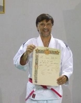 El Mtro.Jorge Juri luce orgulloso el Pergamino entregado por sus alumnos.