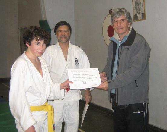 Lucas Zoccola recibe su certificado de Graduaciòn en manos del coordinador de la Escuela de Iniciaciòn Deportiva del EMDeR Prof. Jorge Regatuzzo.