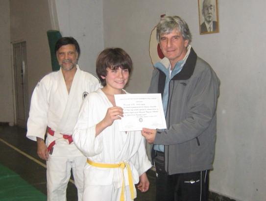 Vìctor Ayala recibe su certificado de Graduaciòn en manos del coordinador de la Escuela de Iniciaciòn Deportiva del EMDeR Prof. Jorge Regatuzzo.