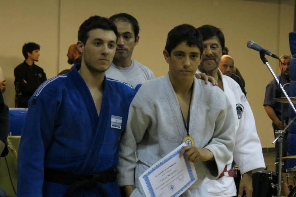 El Profesor de C.A.Peñarol Kevin Juri entrega una distinción a deportista de Ju Jitsu.