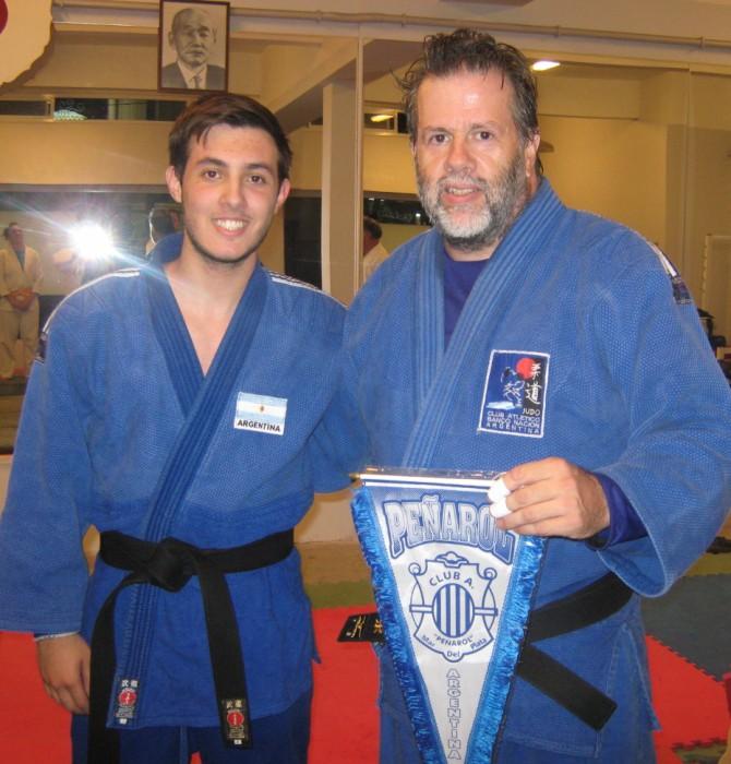 Gustavo Valle  con el Banderín de Club Peñarol que le entregó Kevin Juri.