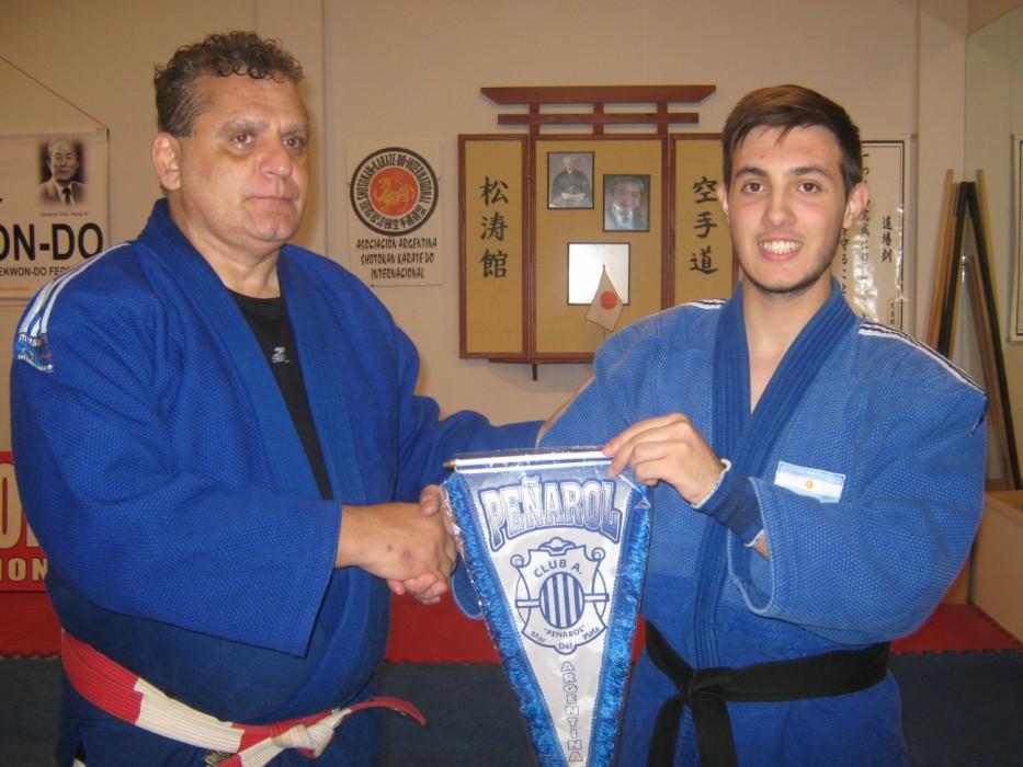 El Profesor de Peñarol Kevin Juri entrega al Maestro Aníbal Janeiro  el Banderín de la institución.