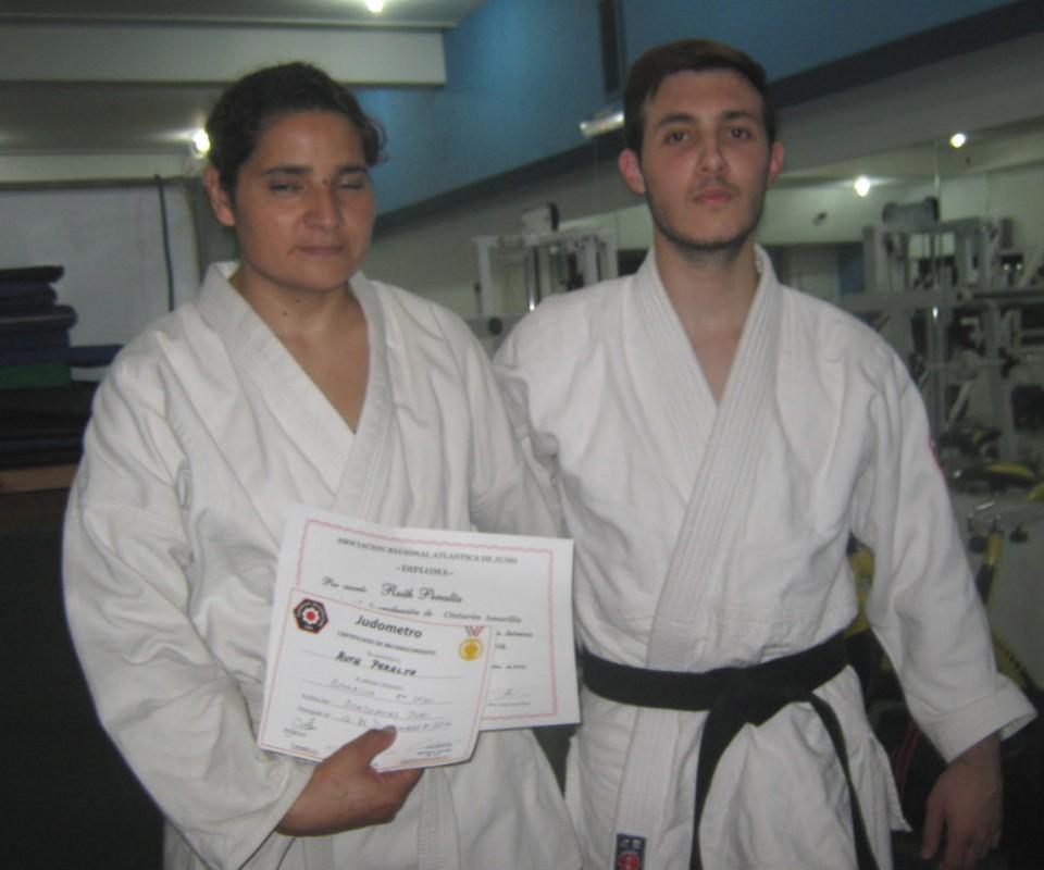 El Profesor Kevin Juri le entrega a Ruth Peralta su Diploma de Graduación Kyu.